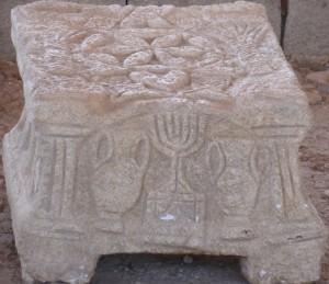 Mit Reliefs versehener Kalksteinblock in der Synagoge (Lesepult?) (Foto: M. Hölscher 2014).